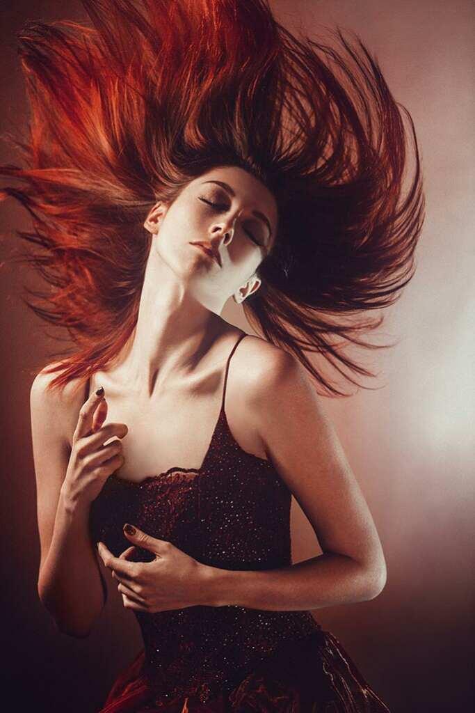 Портрет девушки в прыжке с длинными рыжими волосами