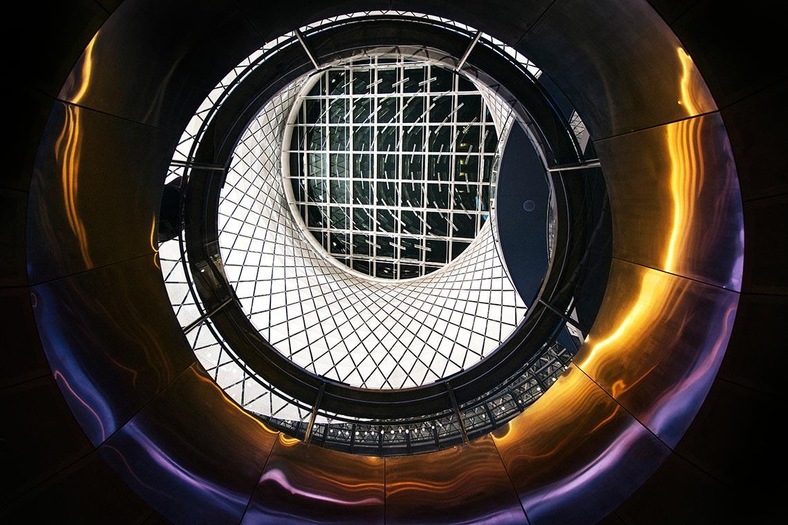 """База для фона арта """"Overlord Star Knights"""".  На изображении представлено круглое окно, закрытое решёткой, с овальным туннелем или помещением. На стенах помещения жёлтые и фиолетовые блики."""