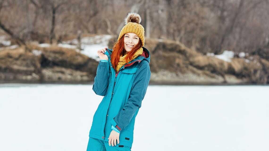 Русская рыжая девушка позирует у реки в горнолыжном костюме и жёлтой вязаной шапке
