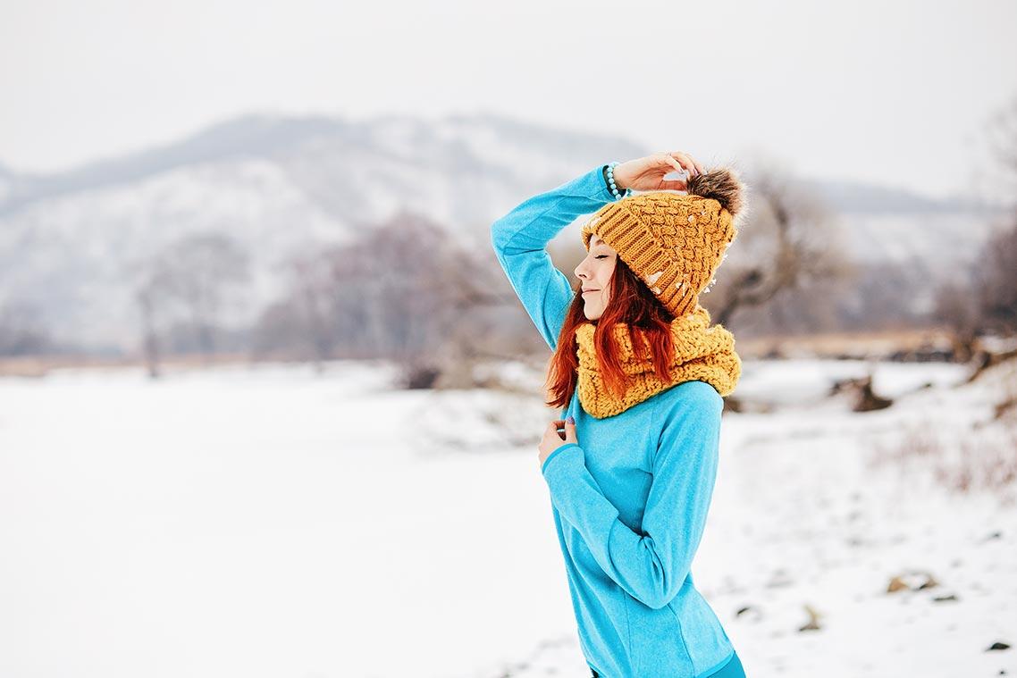 Фото рыжей девушки, зима 2019 года, Приморье. Рыжая девушка в голубой одежде в тёплой оранжевой шапке и оранжевом шарфе позирует на фоне снега и гор