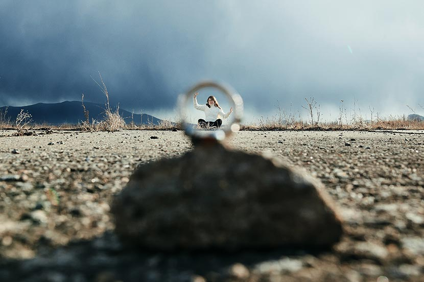 Пример использования кольца для обрамления фото. На кадре девушка сидит внутри кольца и придерживает его руками. На фоне - мрачное грозовое небо.  Автор фото - Tengyart