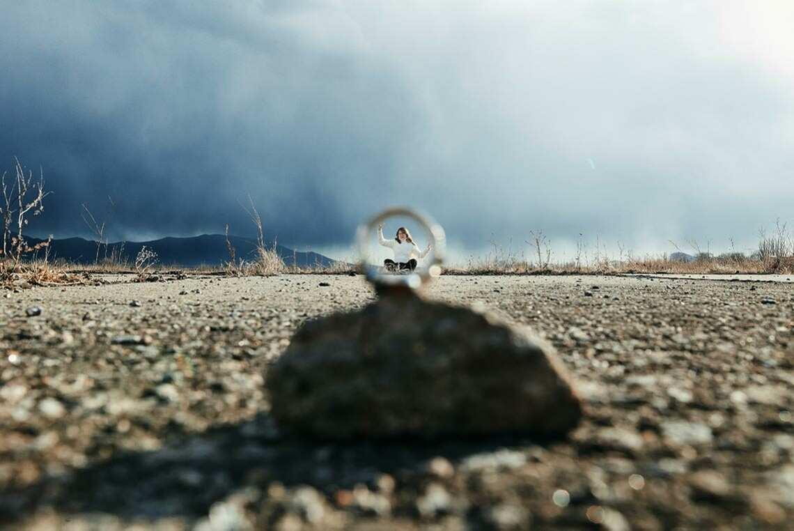 Пример использования фрейминга для создания сюрреалистических фигур.  На фото - кольцо, расположенное на камне. В центре кольца - девушка, держащая его руками. Вокруг кольца мрачные тучи.