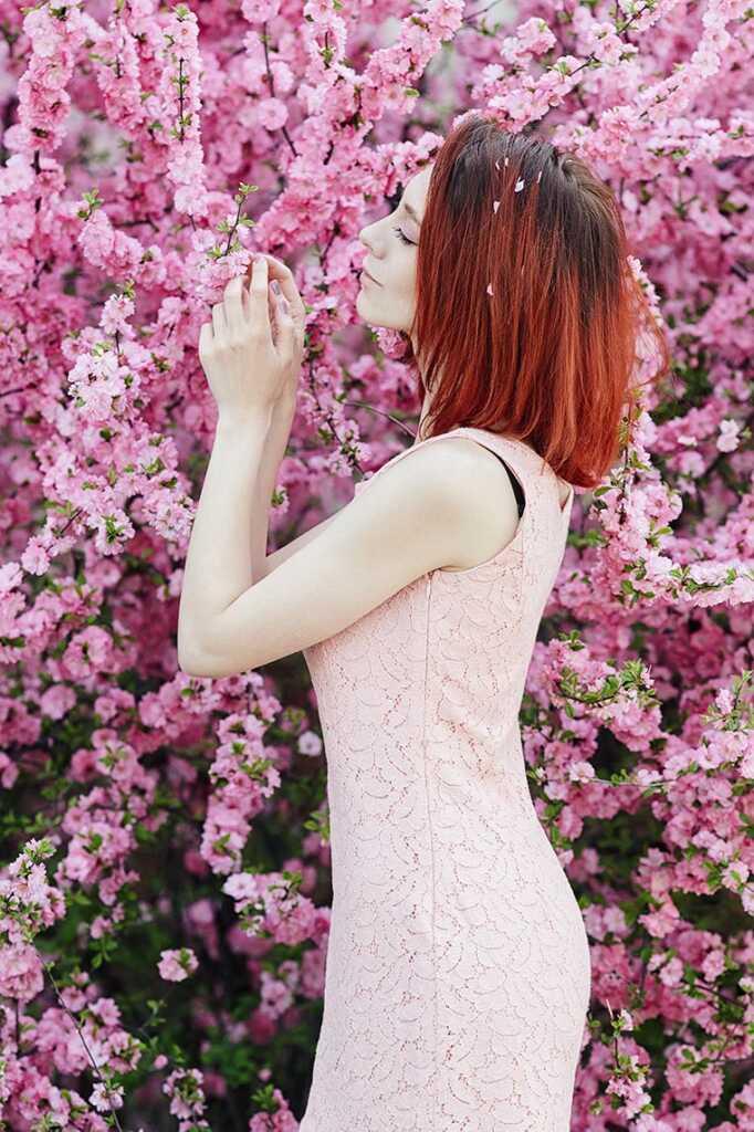 Рыжая девушка позирует в цветущем саду в Приморье