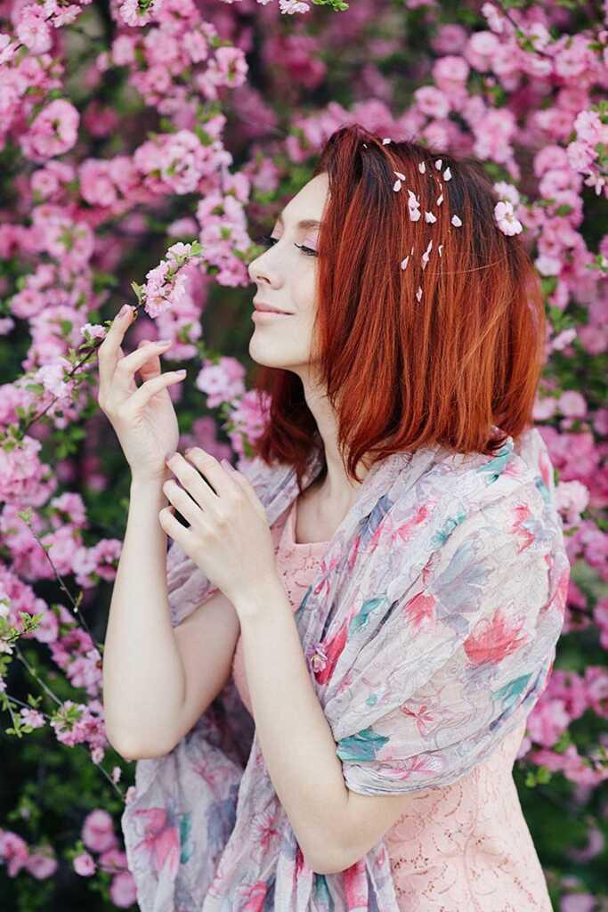 Прекрасная рыжая женщина в цветущей вишне