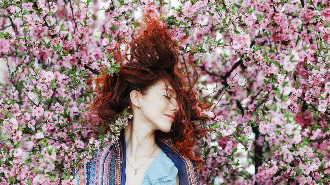 Девушка в цветах с рыжими пышными волосами