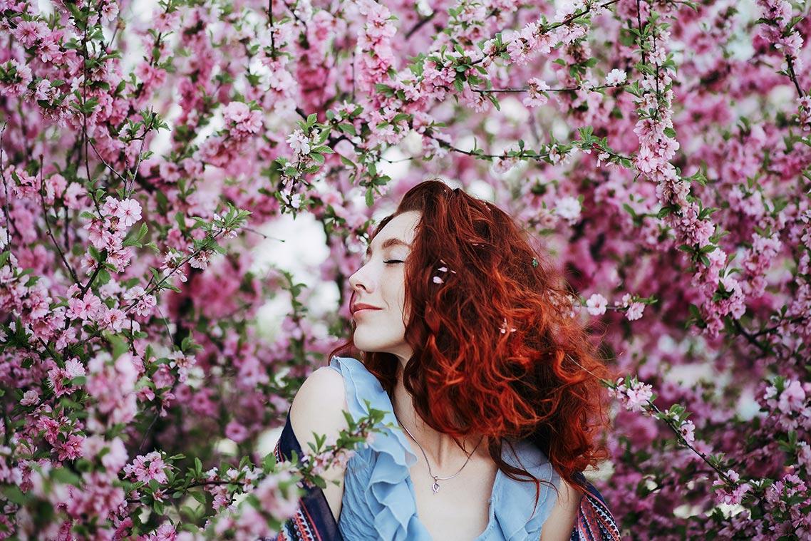 Рыжая девушка томно прикрывает глаза на фоне цветущей японской вишни