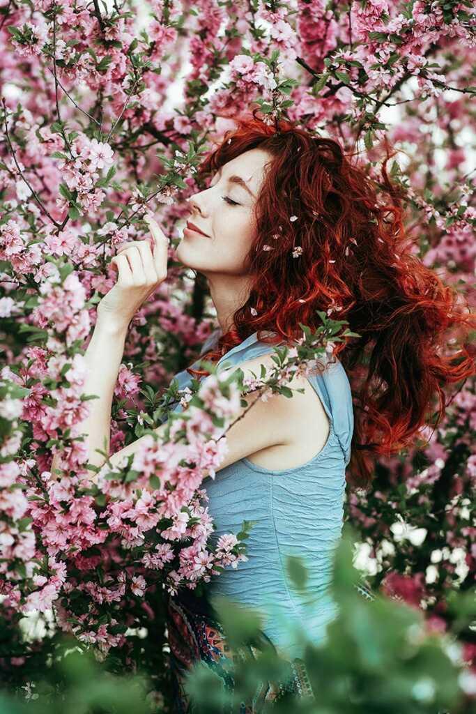 Красивая рыжая девочка в цветущем саду