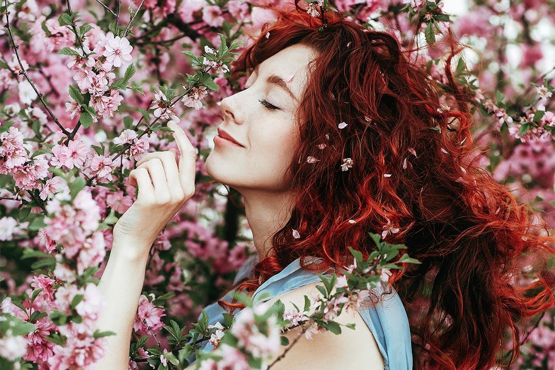 Рыжая девушка с растрёпанными волосами позирует в саду