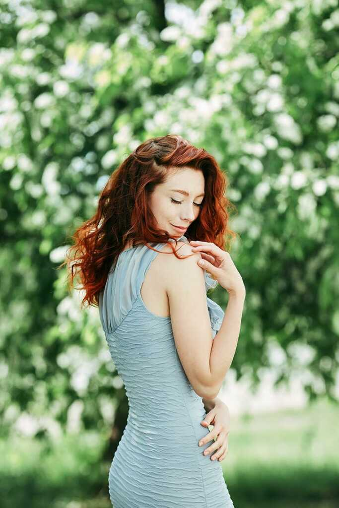 Красивая рыжая девочка позирует на фоне цветущей черёмухи, место съёмки - Золотая Долина