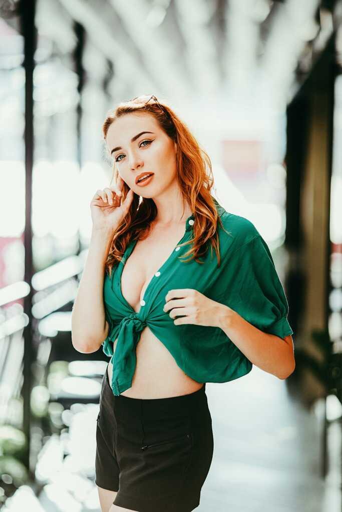 Рыжая девушка в зелёной рубашке сексуально позирует