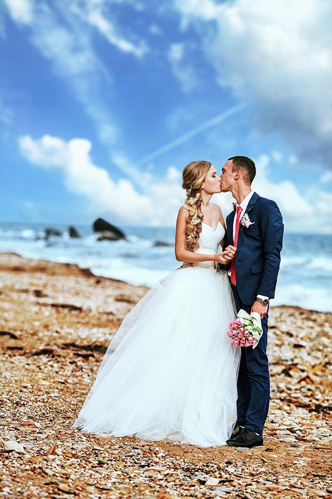 Выездная свадебная фотосессия для влюблённых в Приморском крае. пара целуется, на фоне - каменистый пляж, море и облака