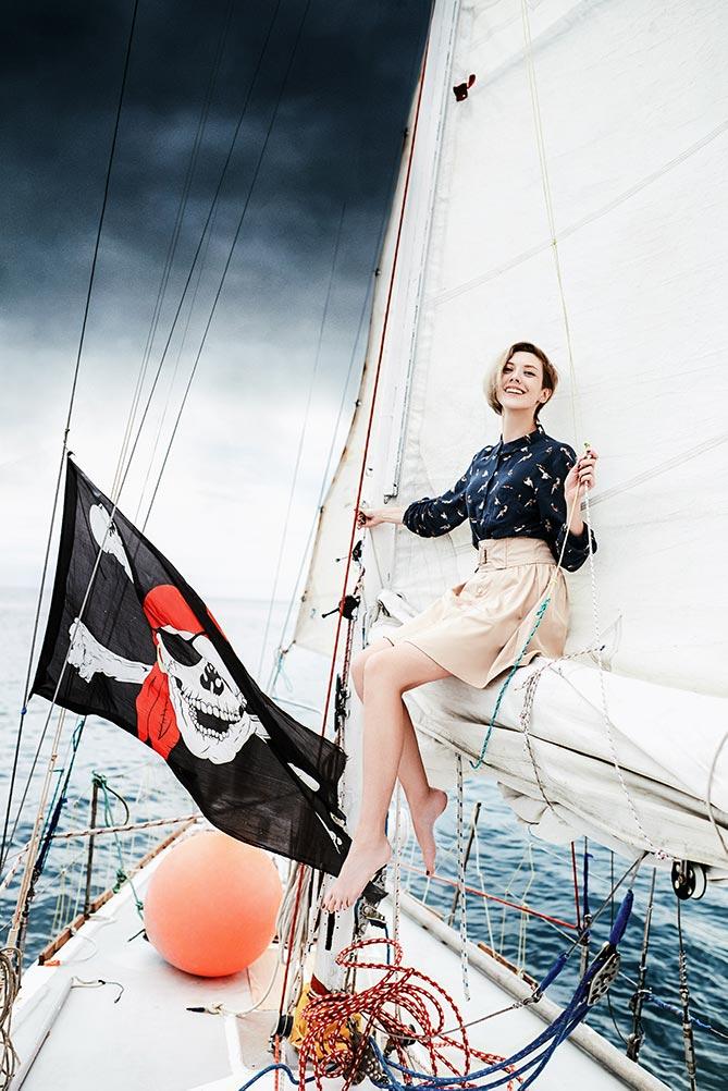 Девушка позирует на яхте в море на фоне пиратского флага