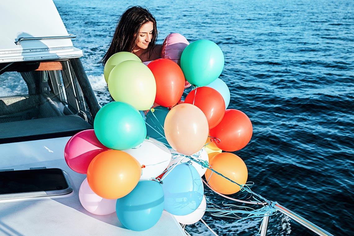 Девушка с шариками готовится к фотосессии в море
