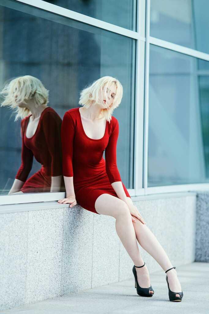 Блондинка в алом платье сидит у театра. Портретная фотосессия на улице во Владивостоке.