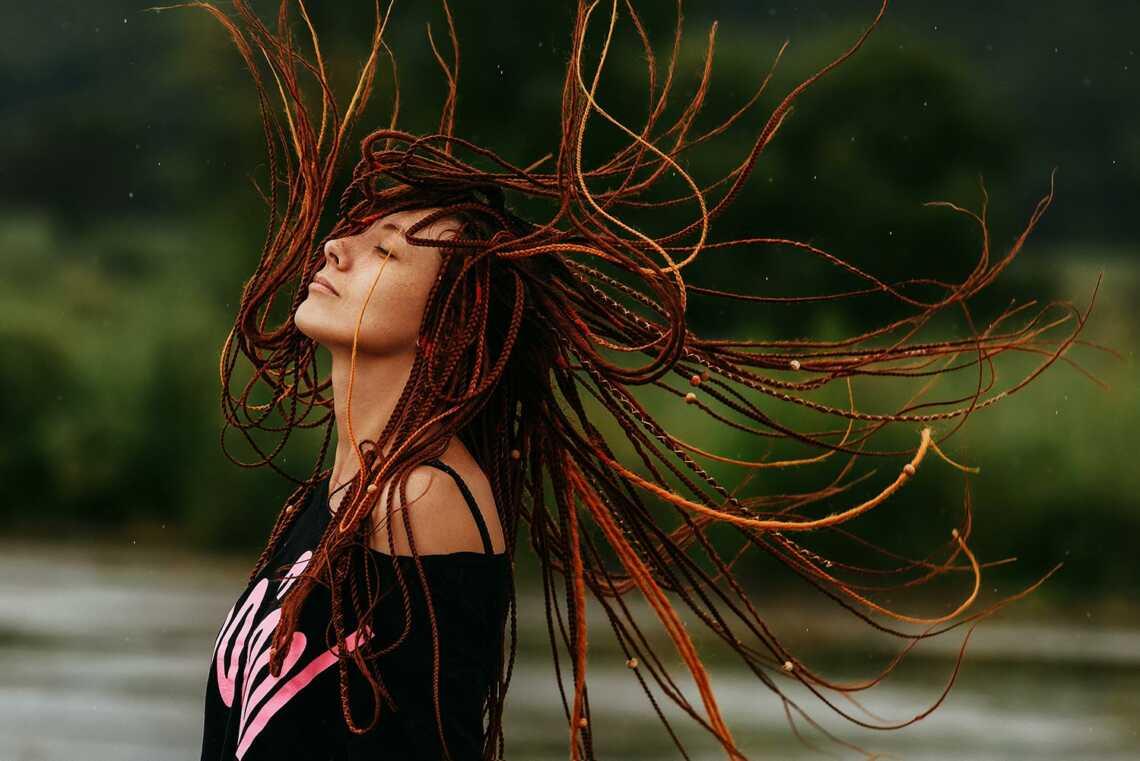 Девушка с дредами прыгает под дождём