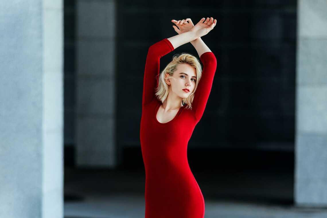 Блондинка в красном платье позирует на парковке, пример фотосессии во Владивостоке.