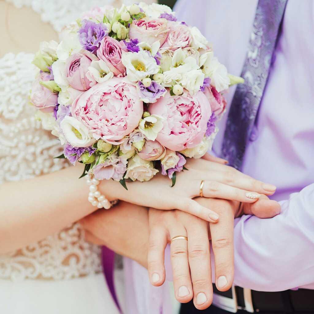 Свадебный букет с руками и кольцами крупным планом
