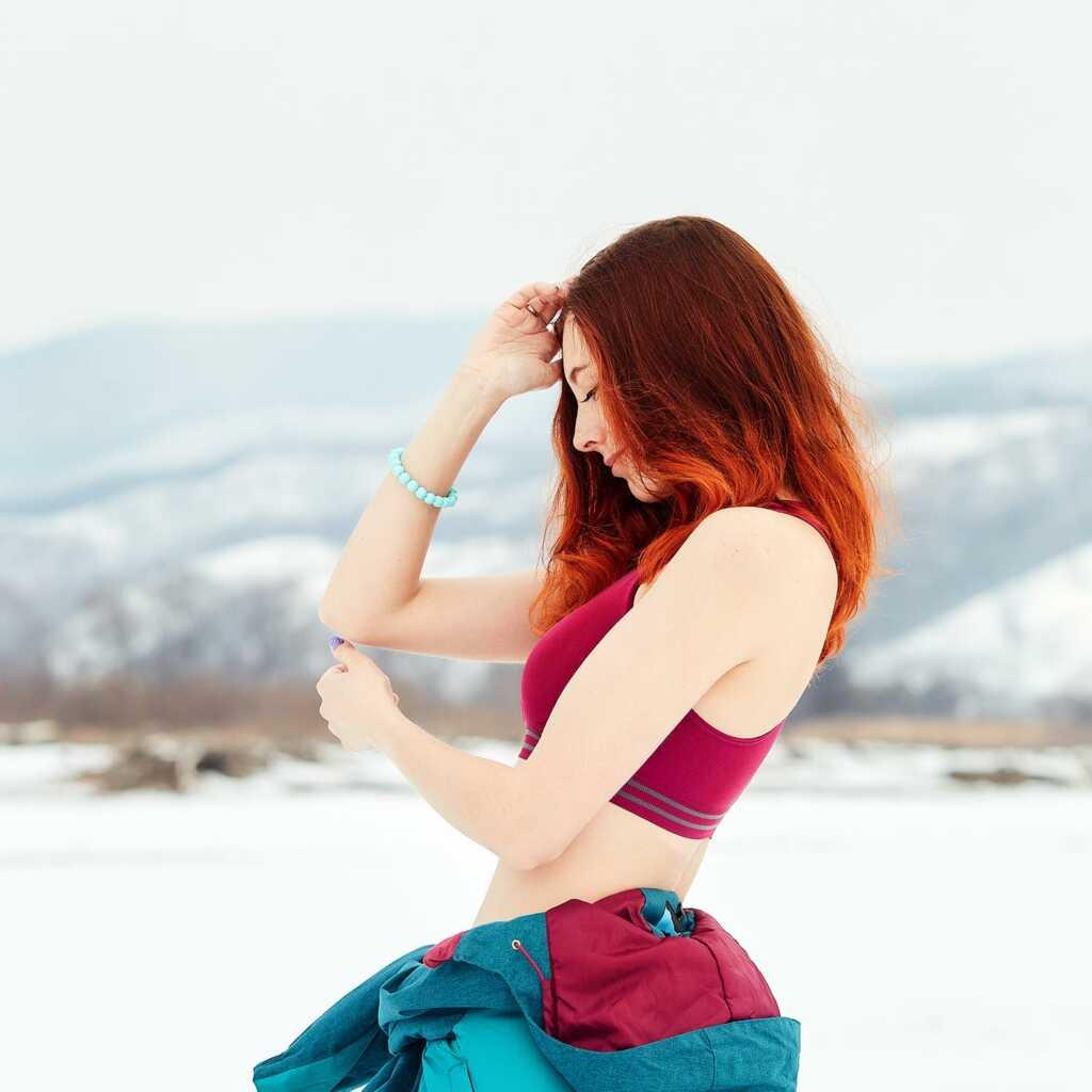 Спортивная фотосессия на улице зимой, автор - портретный фотограф Tengyart. Фото с рыжей девушкой в купальнике на фоне снега и гор.