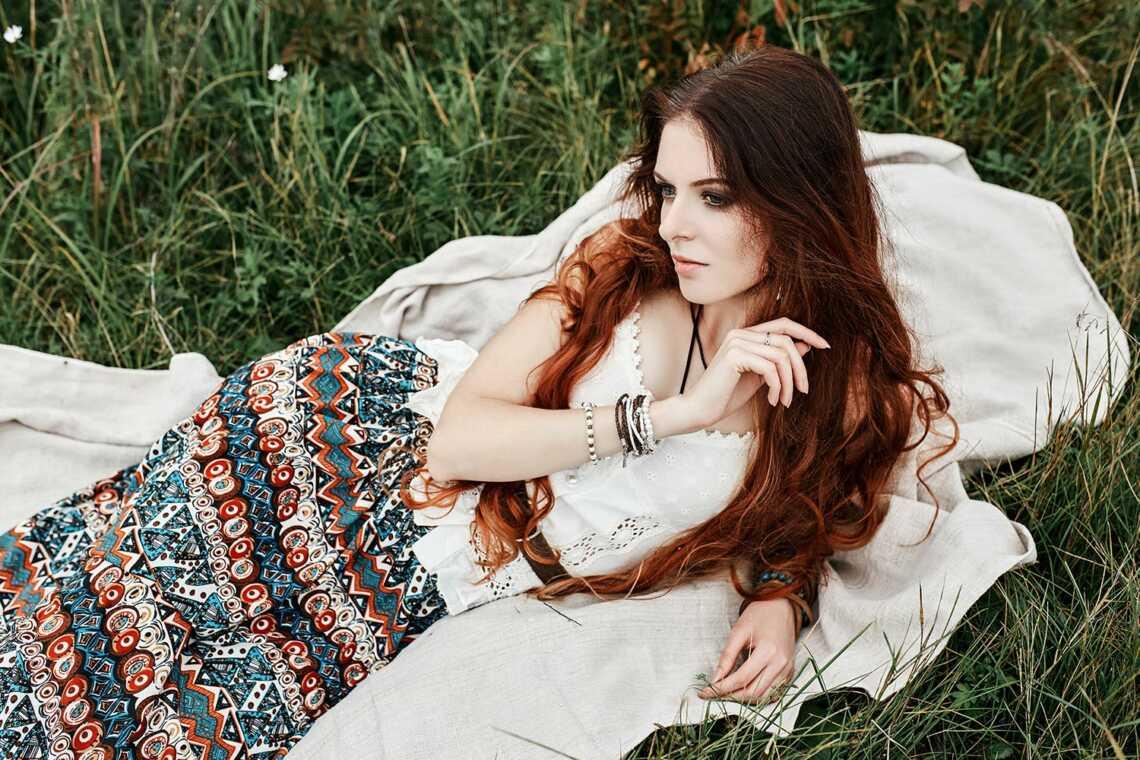 Рыжая девушка в платье с этническими узорами лежит на покрывале в траве