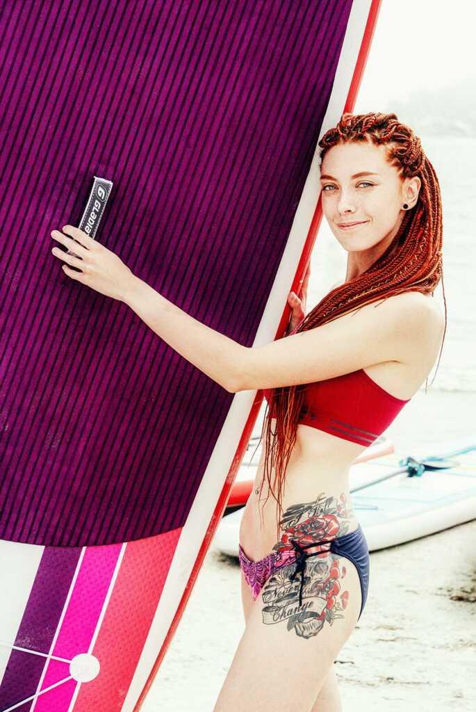Рыжая девушка в белье держит доску для сёрфинга.