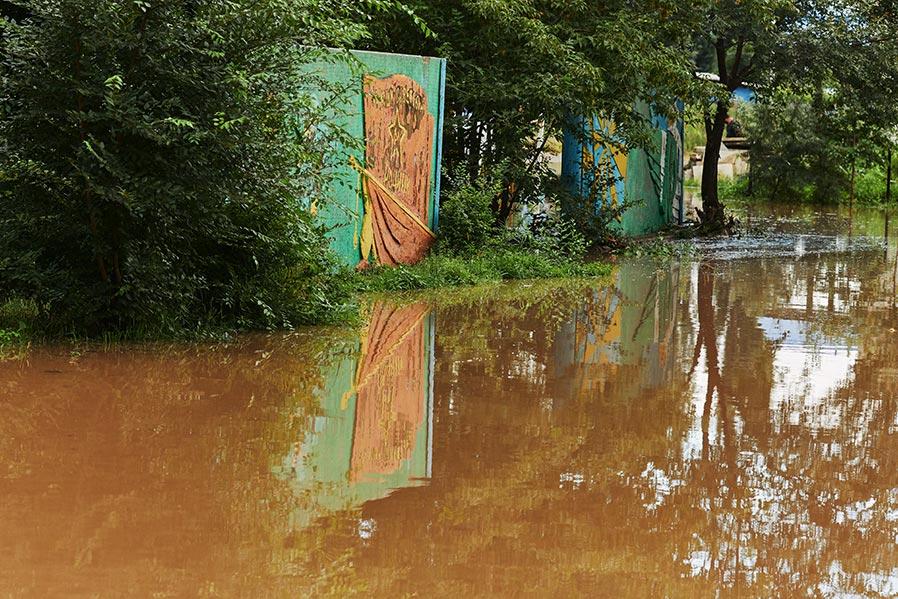 Затопленная парковка перед домом с изображением советсткой символики и памятной стелой