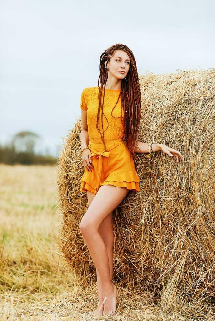 Поза для осенней фотосессии: девушка в лёгком оранжевом платье стоит у стога сена, отставив ножку и смотрит вдаль (фотограф Tengyart)