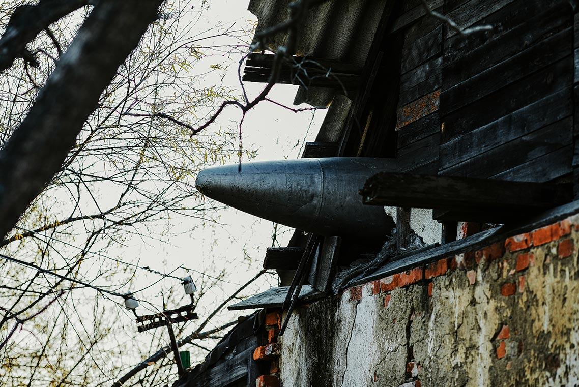 Дом с ракетой, бомбой или топливным баком, торчащим в крыше