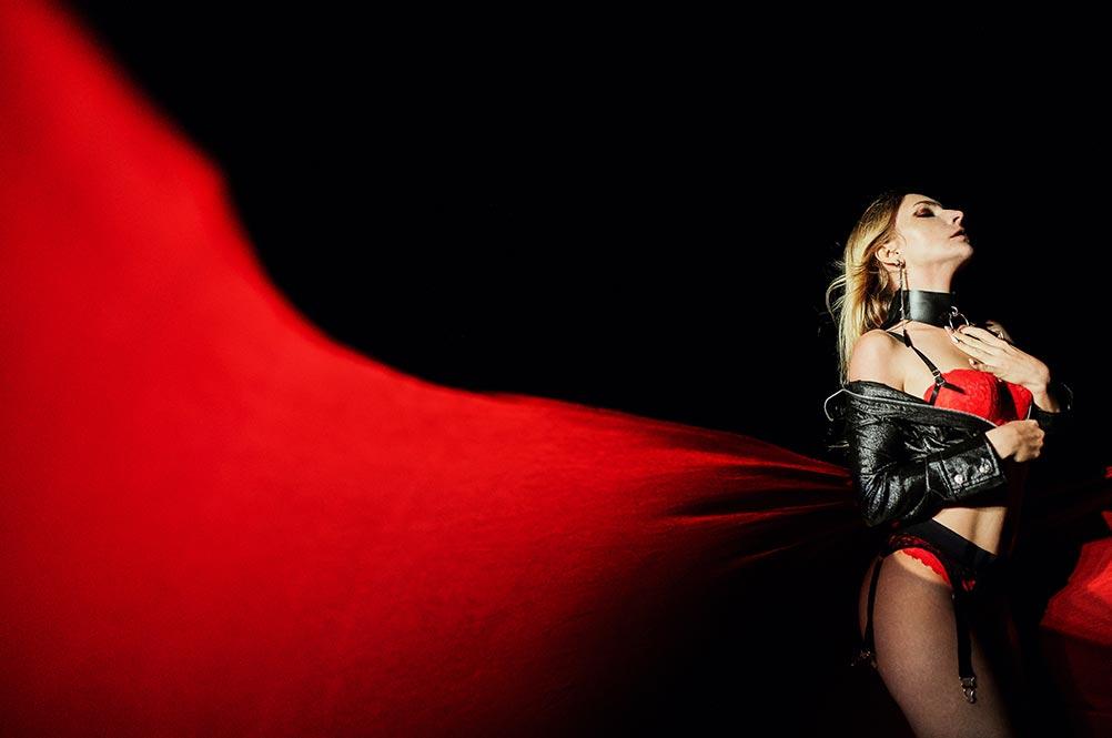 Фотография девушки в белье, сделанная на фоне летящей ткани ночью