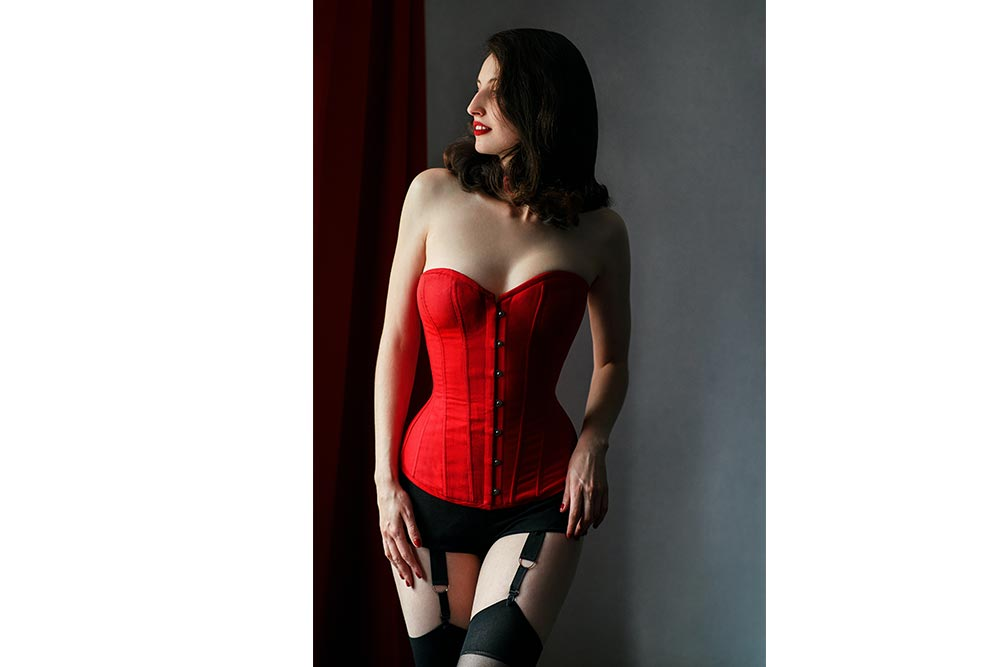 Пинап фотосессия девушки в красном корсете с чулками
