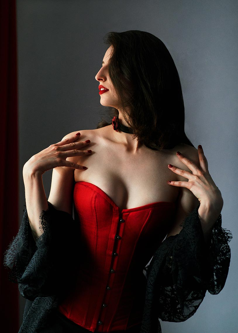 Девушка в красном корсете с чёрной накидкой крупным планом