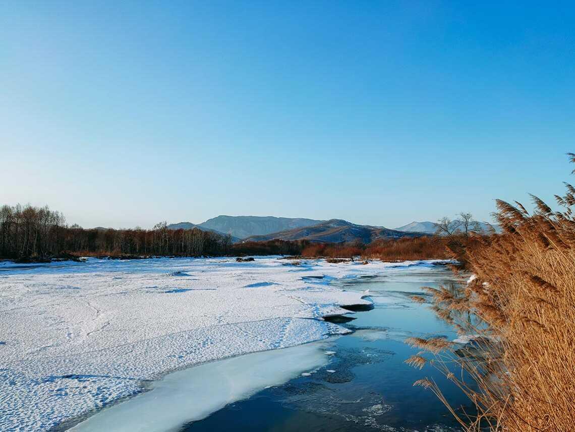 Фотография заснеженной реки с горами вдали. Фон с рекой и горами для рабочего стола в высоком разрешении.