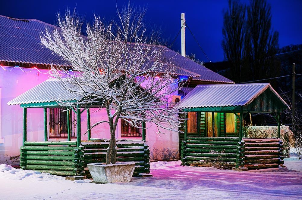 Зимняя фотография с деревянными беседками и неоновой подсветкой