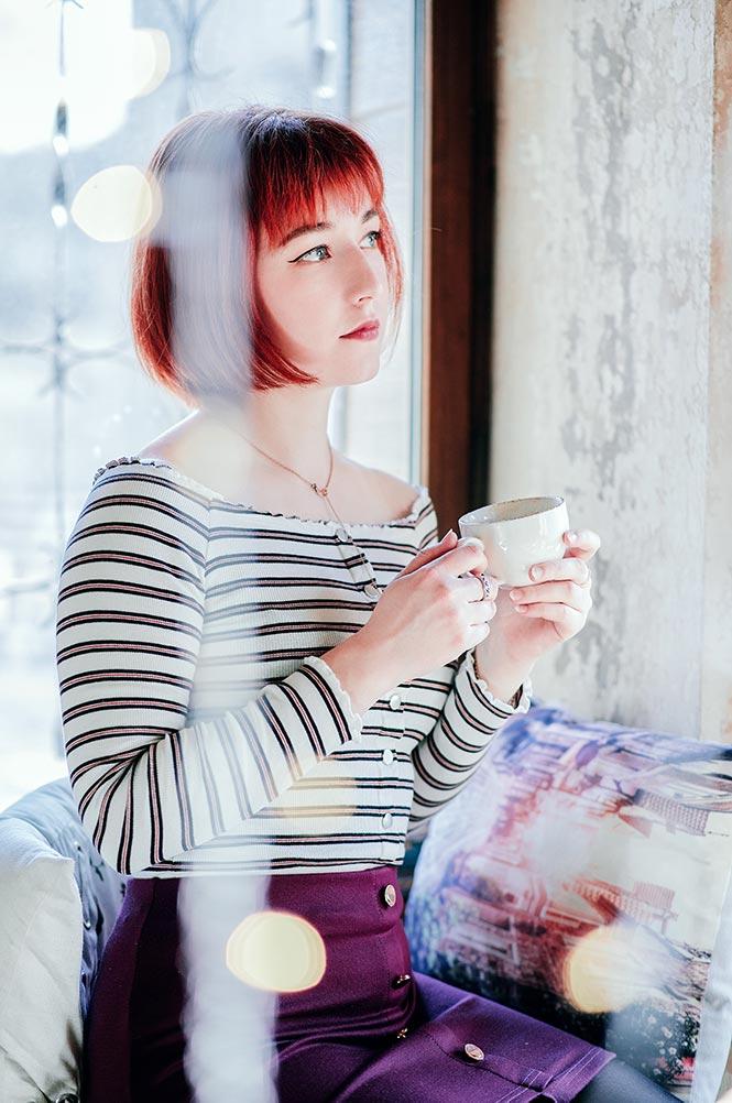Фотография девушки в кафе с чашкой в руках и боке на переднем плане
