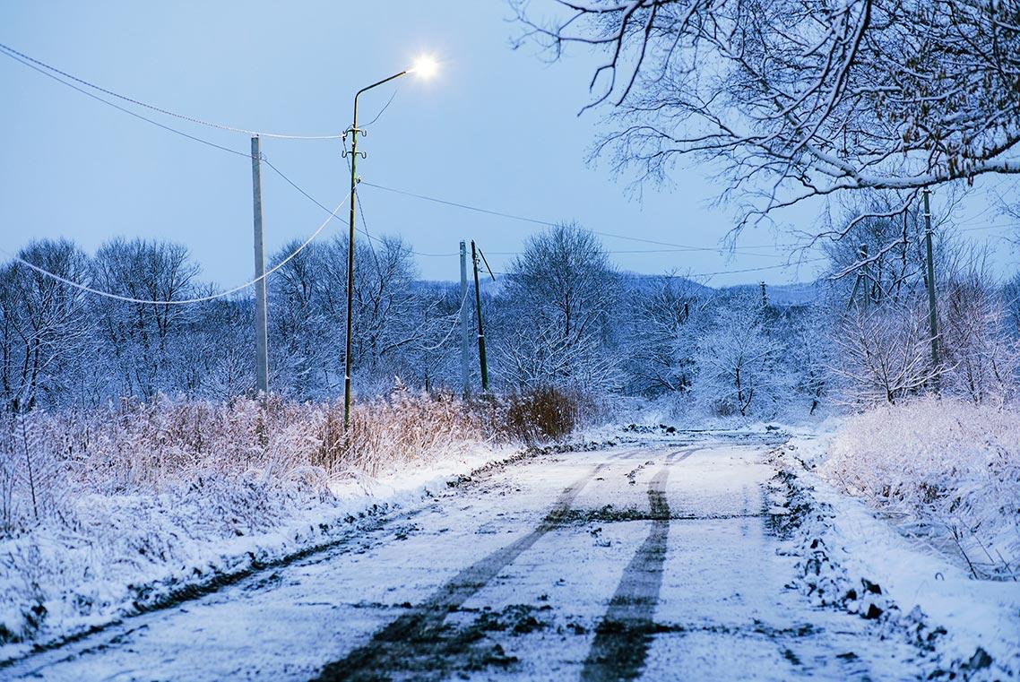 Фотография пустынной сельской дороги, безлюдной и усыпанной снегом