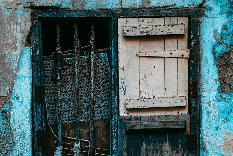 Голубая дверь с решёткой и царапинами