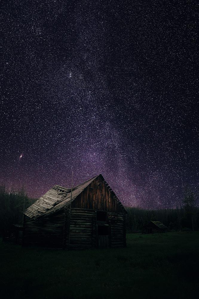 Звёздное небо и пейзаж с мрачным домом на переднем плане.Тёмная картинка для смартфона.