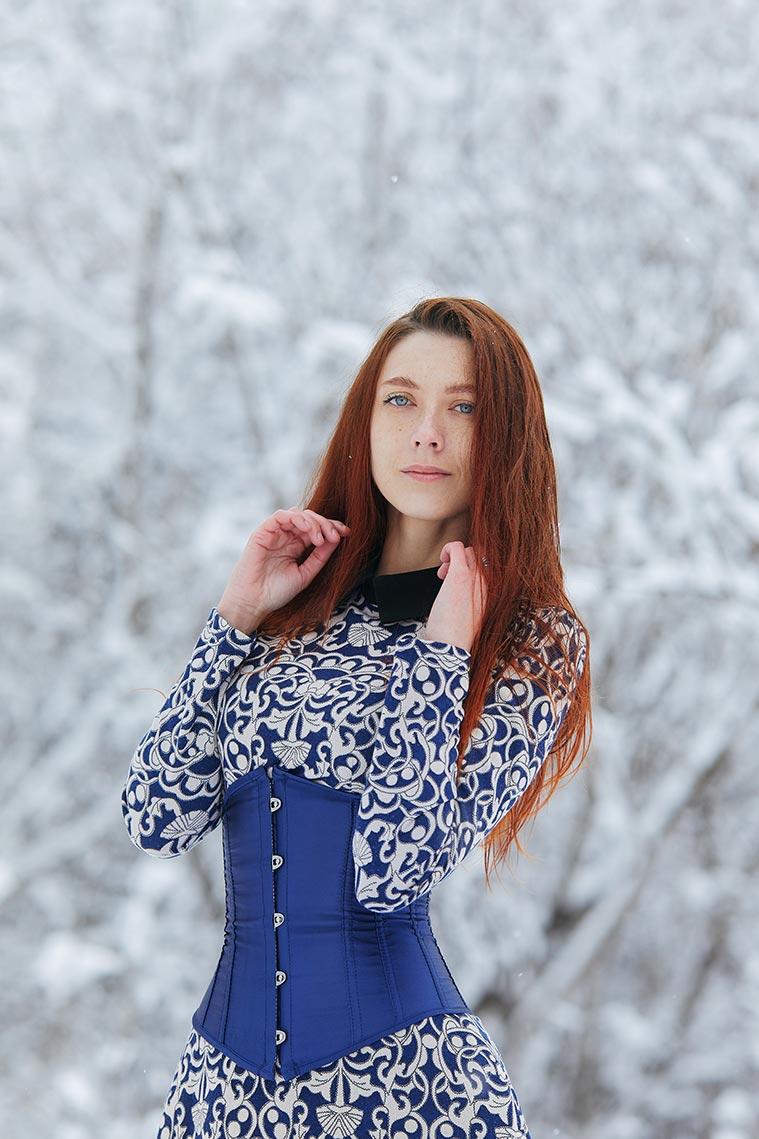 Красивое фото с рыжей девушкой в синем корсете на фоне снежного леса и советы по съёмке в метель от Tengyart