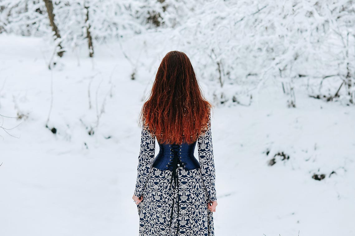 5 советов по съёмке портретов и пейзажей в снегопад, пункт 4 - выбор портретных и телеобъективов для зимней фотосессии. На фото рыжеволосая девушка стоит спиной к камере в синем корсете и узорчатом платье на фоне размытого снежного леса.