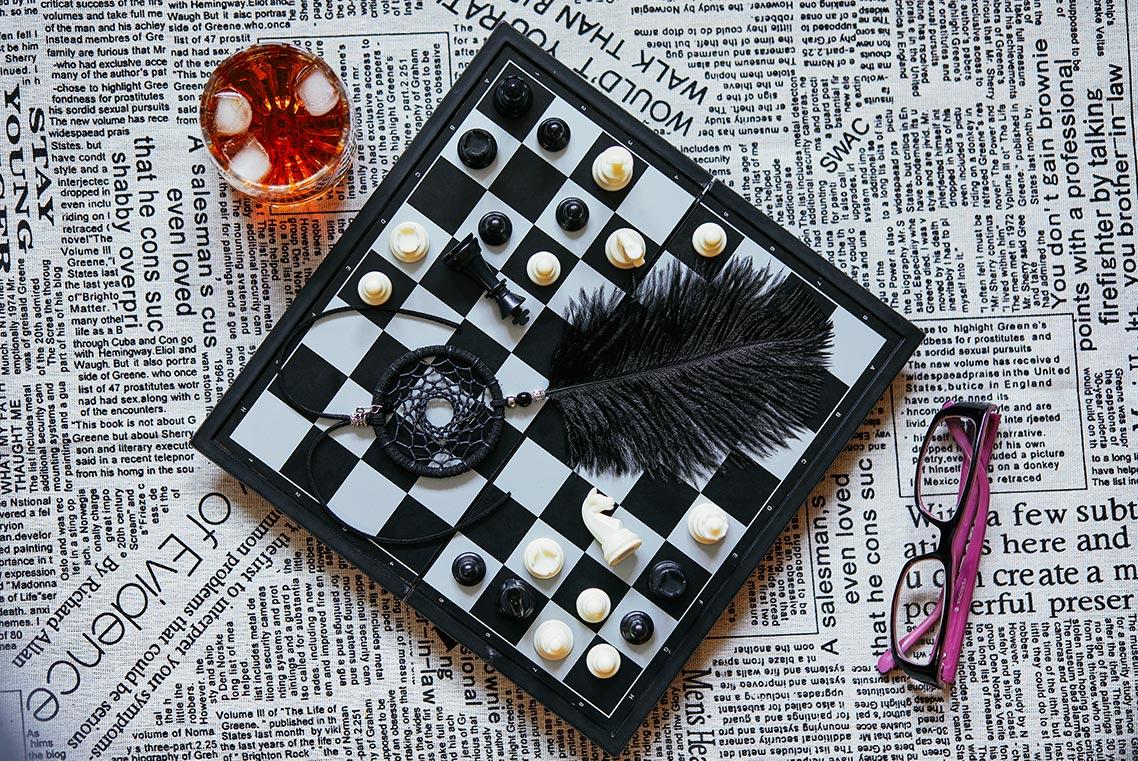Как убрать белые точки в фотошопе - инструкция от фотографа Олега Мороза. На картинке изображена шахматная доска с чёрным ловцом снов и стаканом коньяка
