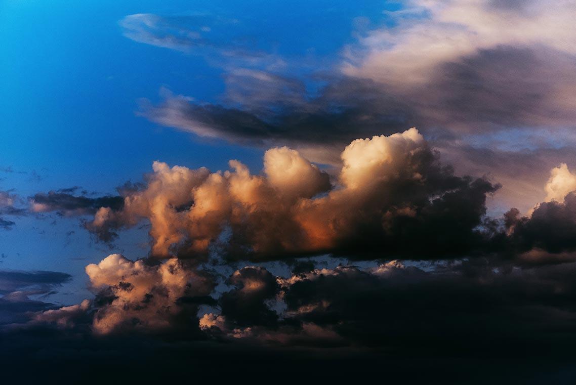 Насыщенные оранжевые закатные облака на фоне чёрных туч и голубого неба (заставка для смартфона)