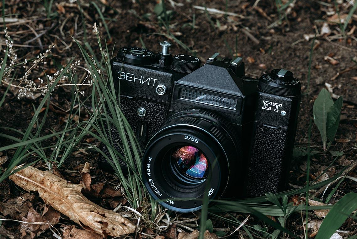 Красивая ретро камера на земле в тёмно-зелёной траве