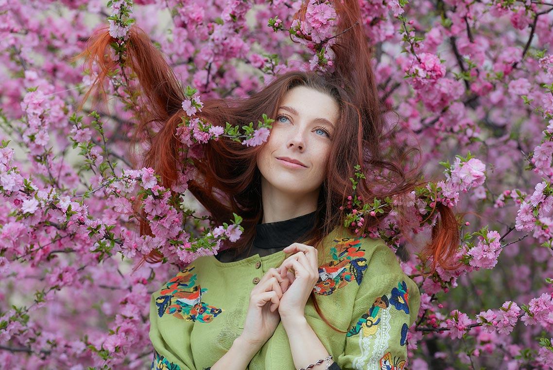 Портретная фотосессия в цветущем саду в Золотой Долине (на фото изображена красивая русская рыжая девушка с длинными волосами, позирующая в цветах)