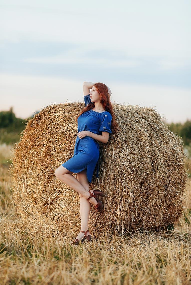Рыжая девушка с длинными волосами в синем платье на фоне стога сена (заставка для рабочего стола смартфона). Фотограф Олег Мороз (Tengyart)
