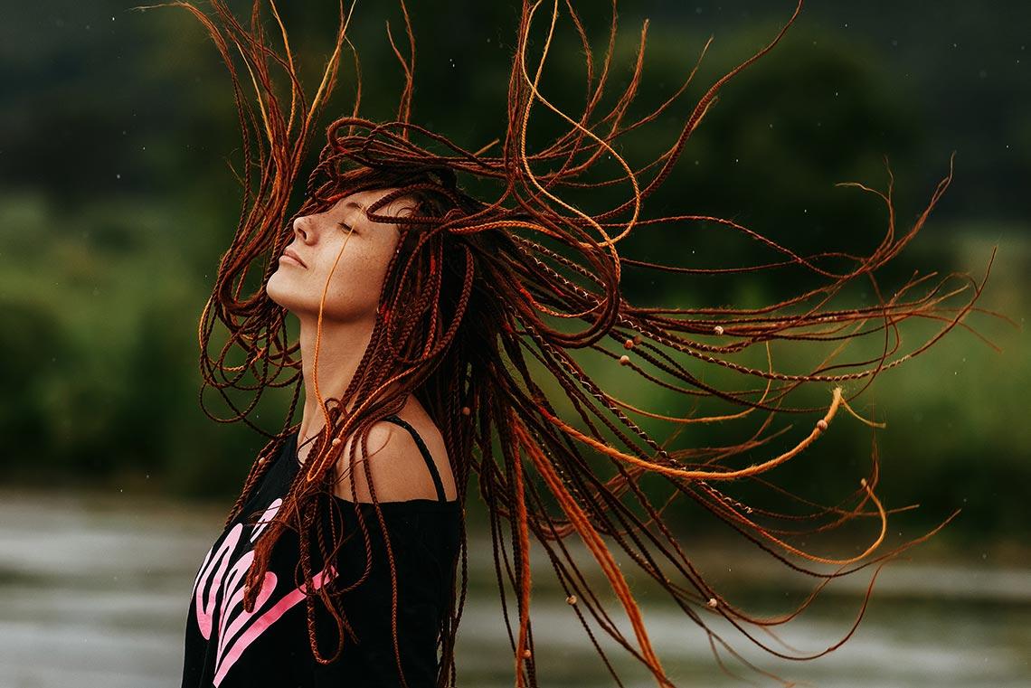 Фотография девушки с рыжими дредами (портрет девушки с дредами, прыгающей во время дождя)