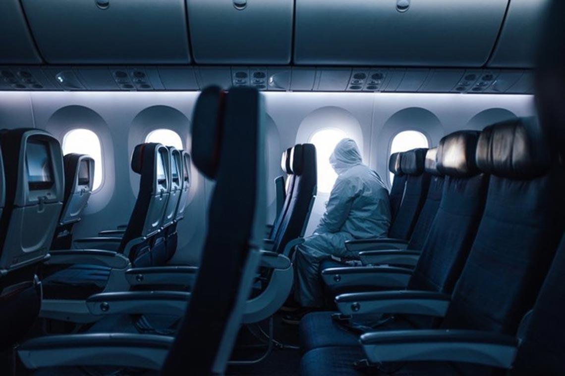 Фотография одинокого пассажира в медицинском халате, маске и перчатках на борту самолёта во время пандемии коронавируса (проект Covid Street)