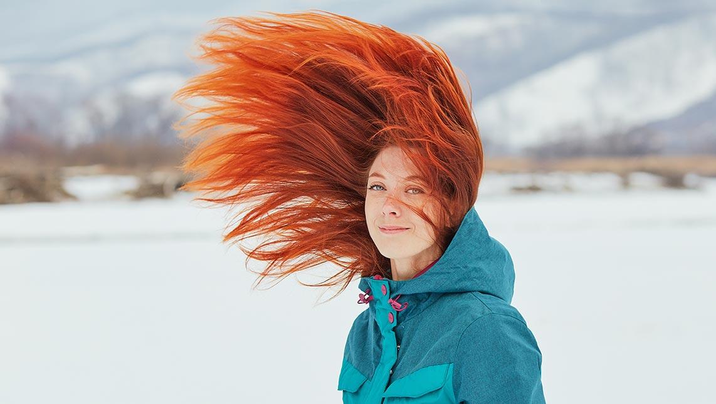 Фотография рыжей девушки в синей куртке с летающими волосами (портрет девушки на фоне снежной долины, фон для рабочего стола)