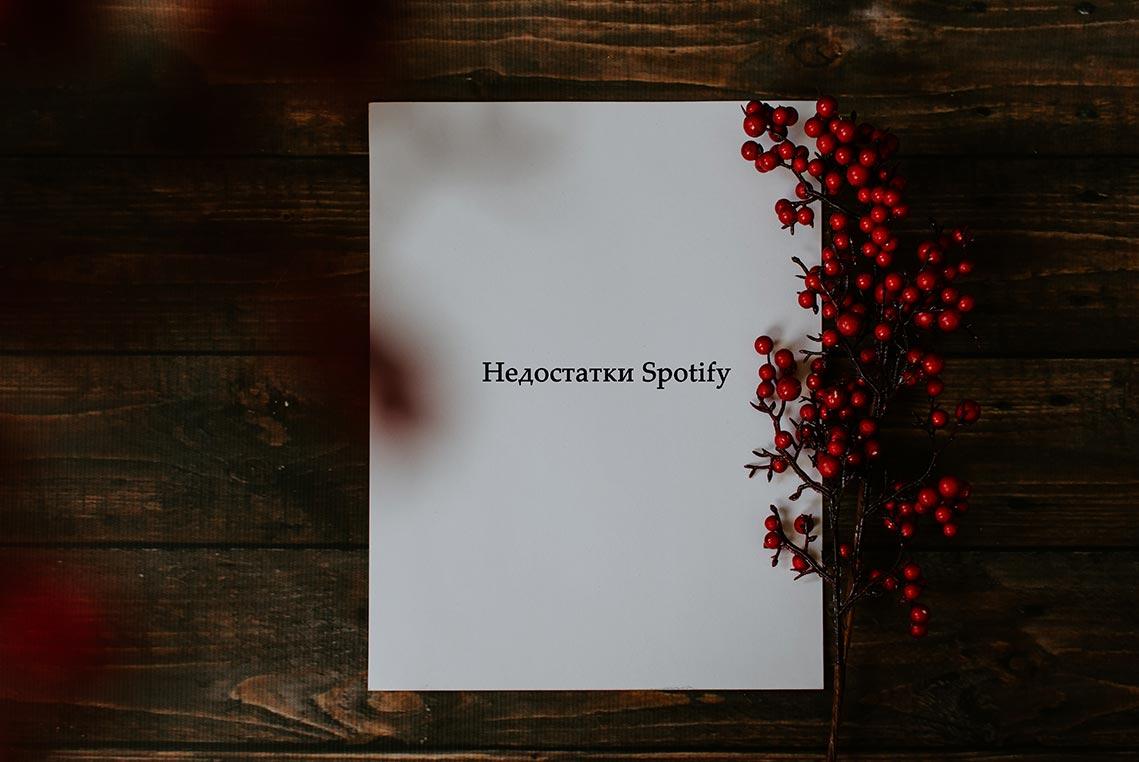 """Белый лист бумаги с красными ягодами на деревянном столе. На листе надпись: """"Недостатки Spotify"""""""