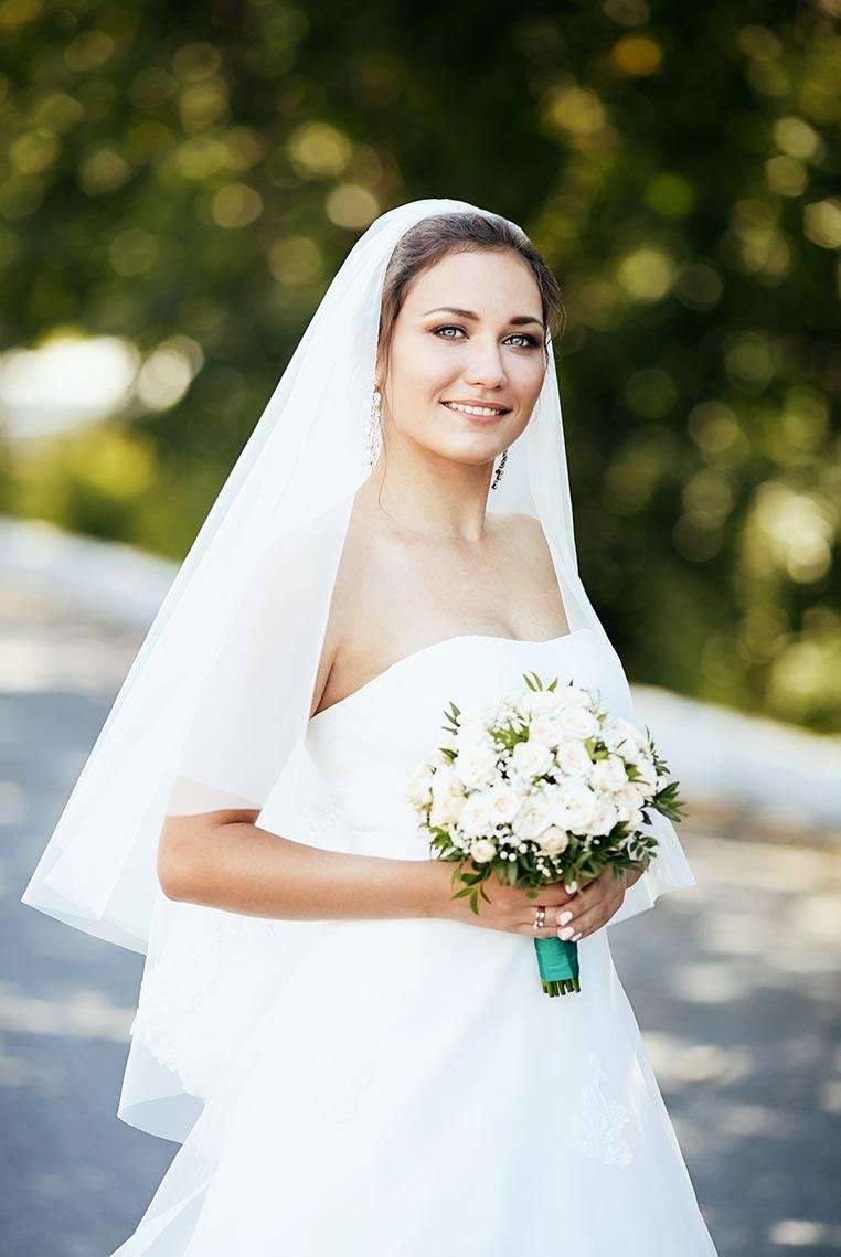 Портрет невесты с букетом с белыми цветами, фатой и размытым фоном (автор - фотограф Олег Мороз)