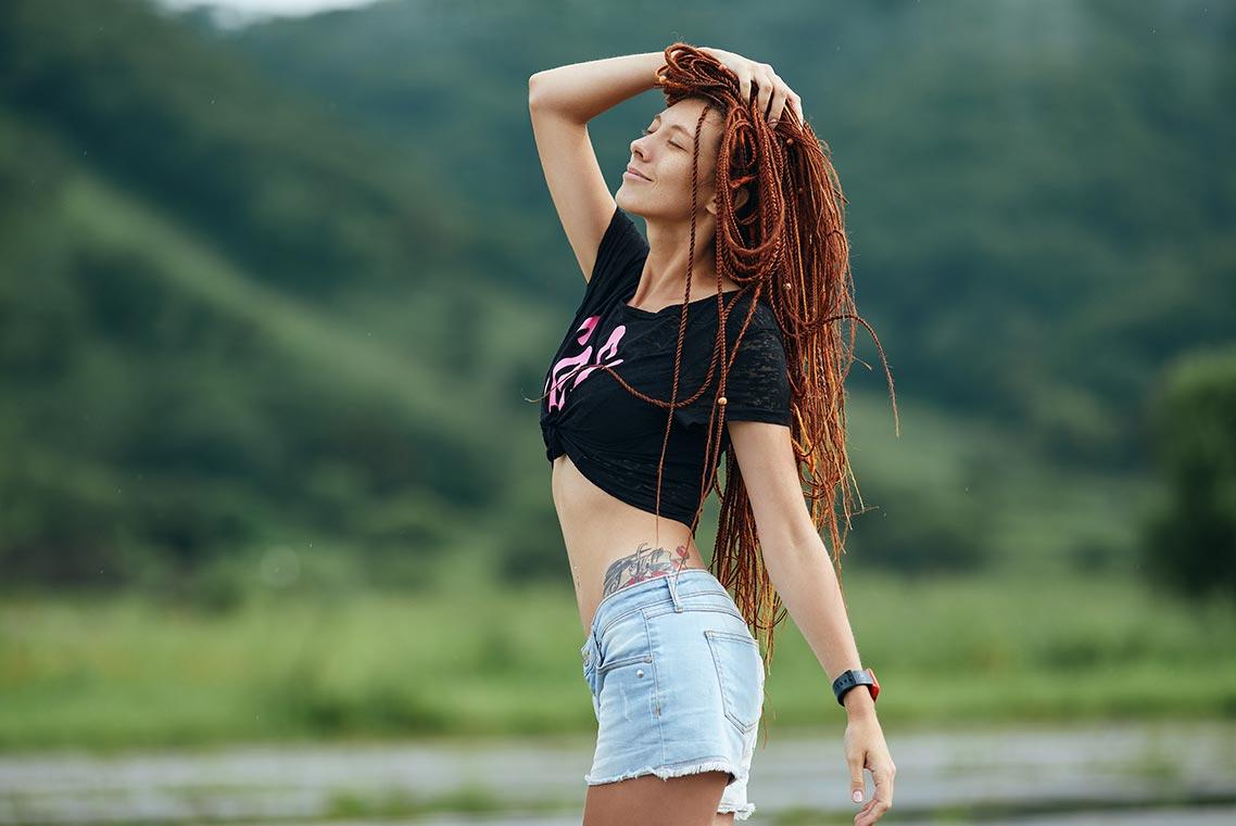 Рыжеволосая девушка с татуировками на фоне размытых сопок - идея для уличной фотосессии на природе