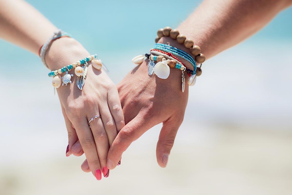 руки влюблённой пары с браслетами из бусин, ракушек и бижутерии ручной работы крупным планом